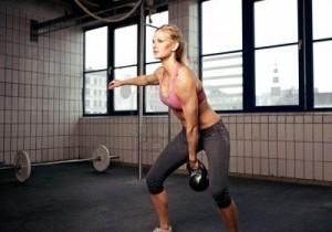 14157960-giovane-fitness-donna-adulta-fare-esercizio-swing-con-un-kettlebell-come-parte-di-un-allenamento-cro
